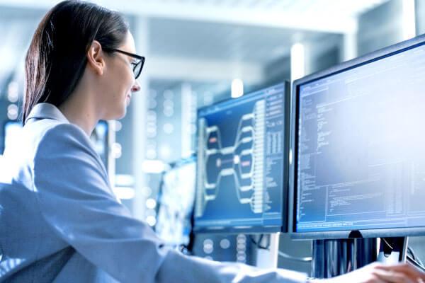 Mitarbeiterin prüft Kommunikationsschnittstelle einer Maschine am Computer